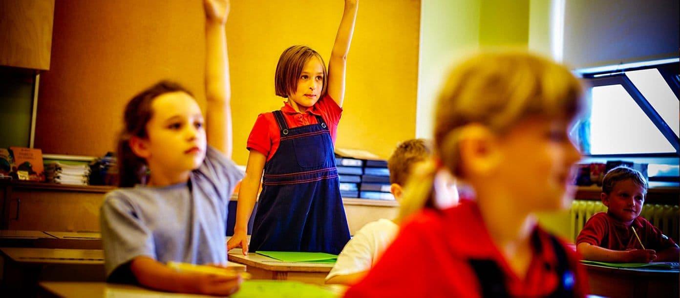 Deux étudiantes de l'Académie des Sacrés-Cœurs levant la main en classe.